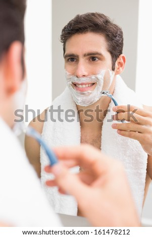 Close up of a handsome young man with reflection shaving in the bathroom