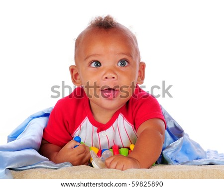 Close-up of a happy biracial baby with big, blue eyes and his blanket and toys.  Isolated on white. - stock photo