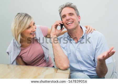 Close-up of a happy casual couple using mobile phone at table in the house