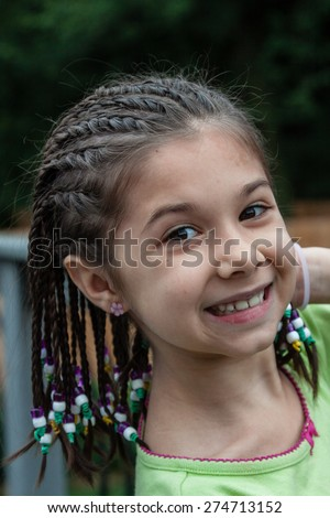 close-up of a happy cute little girl with brown hair in braids
