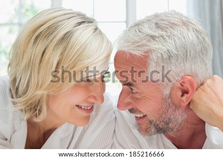 Close-up of a happy mature couple lying in bed at home
