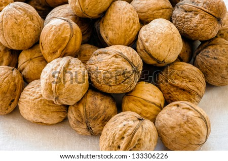 Close up of a heap of dry tasty walnuts on a white tablecloth