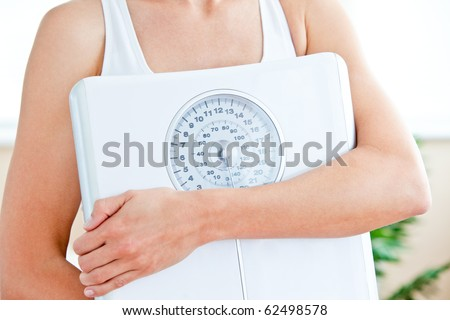 Close-up of a hispanic woman holding a scale in her living-room at home - stock photo