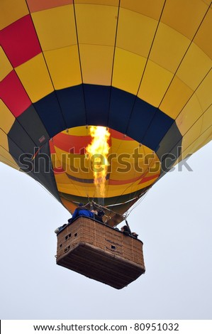 Close up of a hot air balloon in the sky with a basket full of people - stock photo