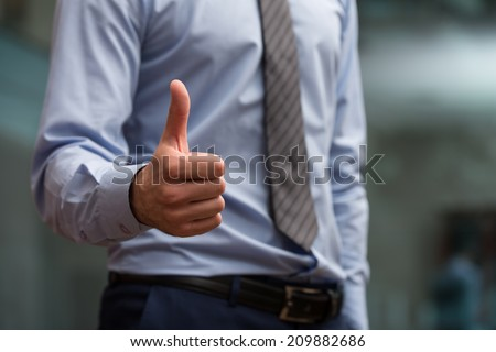 Close-Up Of A Human Hand Showing Thumbs Up On The Foreground