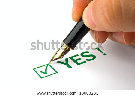 Close-up of a human ticking YES on a questionnaire - stock photo