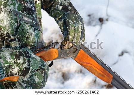 Close-up of a hunter loading his old russian double-barreled over and under shotgun in winter forest - stock photo