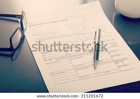Close up of a job application form on desk with pen and glasses - stock photo