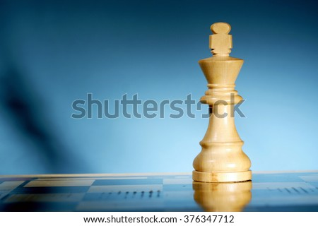 Close-up of a king chess piece on chess board - stock photo