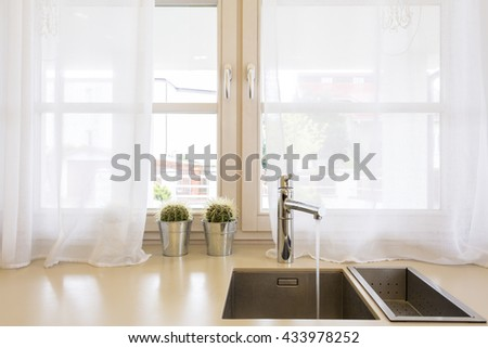 Close up of a kitchen sink, worktop, and window - stock photo