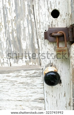 Close Up of a Knob and Lock on a Weatherbeaten Door of an Old House - stock photo