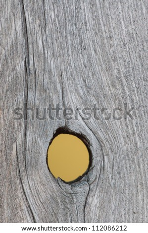 Close up of a knot hole in a weathered board.