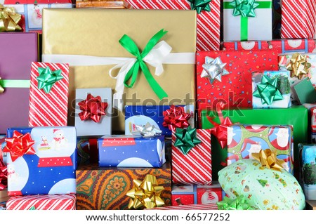 Close up of a large stack of wrapped Christmas presents of varying sizes and shapes. - stock photo