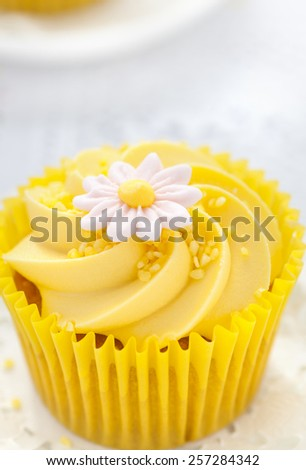 Close up of a Lemon cupcake with butter cream swirl and fondant flower decorations - stock photo