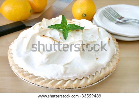 Close up of a lemon meringue pie garnished with fresh mint leaves. - stock photo