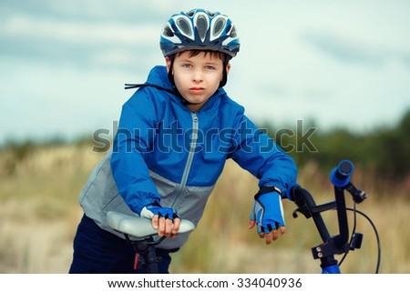 Close-up of a little boy face on bike looking at camera and smiling - stock photo