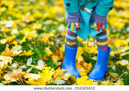 Close up of a little girl in colorful clothes and blue boots outdoors at beautiful autumn park - stock photo
