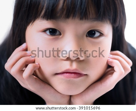 Close-up of a little girl looking at camera.