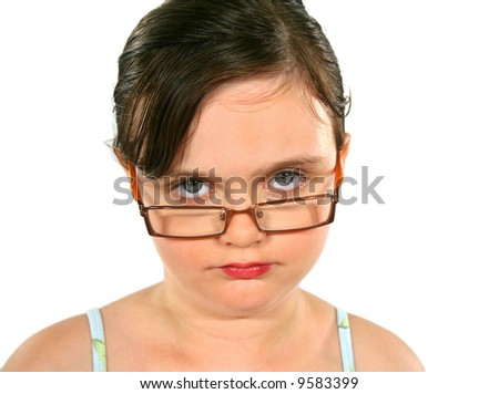 Close up of a little girl with glasses with serious look.