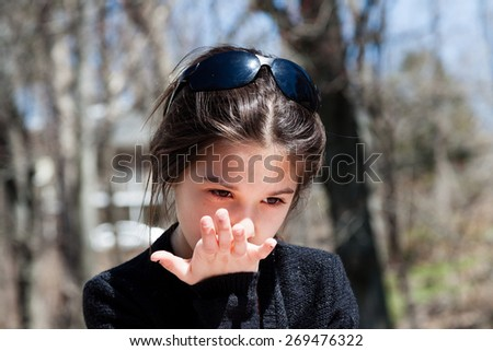 close-up of a little girl with long brown hair, wearing sunglasses  - stock photo