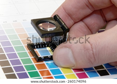 Close-up of a loupe and a hand on a test print - stock photo