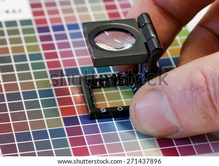 Close-up of a loupe on colorful, blurry inkjet test print with color dark shades in cyan, blue, magenta, red, green, orange, and yellow. Short DOF - stock photo