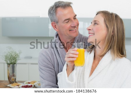 Close-up of a loving couple looking at each other in the kitchen at home - stock photo