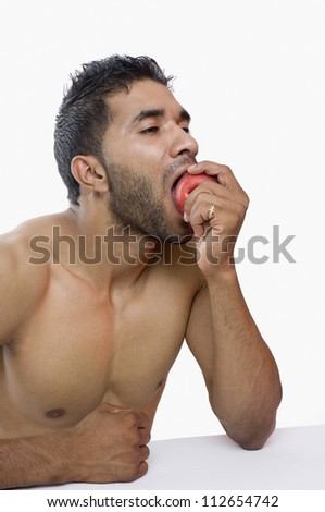 Close-up of a macho man eating apple - stock photo