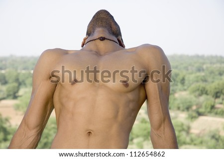 Close-up of a macho man stretching - stock photo