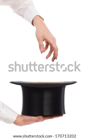 Close up of a magician's hands pulling something out from top hat. Studio shot isolated on white.