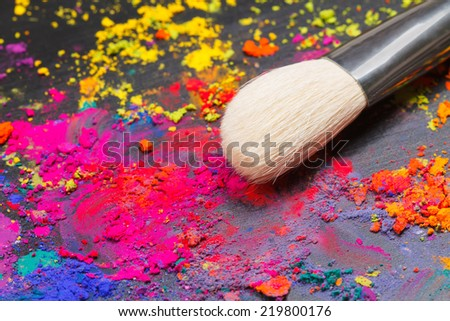 Close-up of a makeup brush  with colorful powder. Beauty concept - stock photo