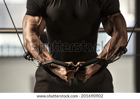 Close-up of a male bodybuilder working out at gym - stock photo