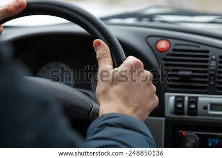 Close up of a male hand on steering wheel. - stock photo