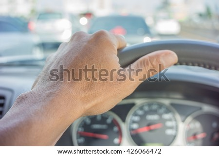 Close-up of a male hand on steering wheel in a modern car in the bangkok(steering wheel on the right)