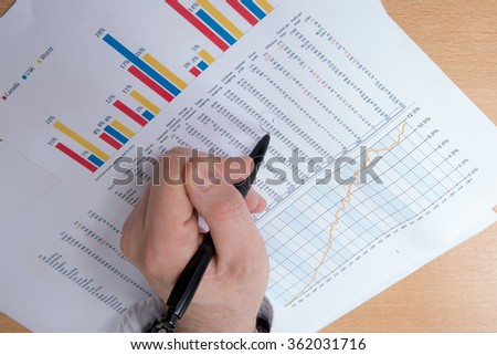 Close-up of a male hands pointing at business document