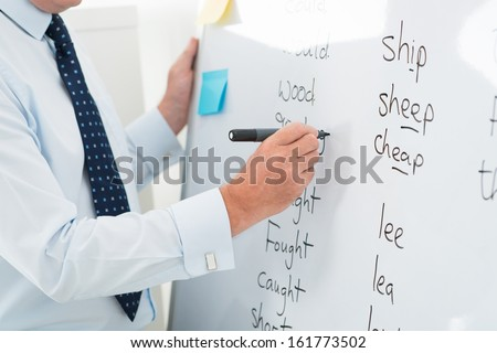 Close-up of a male teacher writing English words on the whiteboard - stock photo