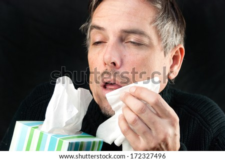 Close-up of a man about to sneeze holding a tissue and the box. - stock photo