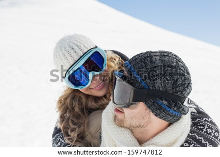 Close-up of a man and woman in ski goggles against snow covered hill - stock photo