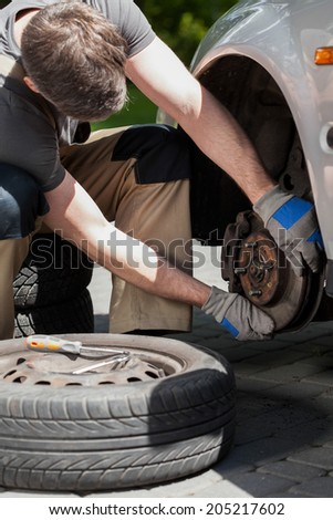 Close-up of a man changing a car brakes - stock photo