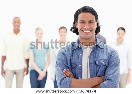 Close-up of a man crossing his arms with people behind against white background - stock photo