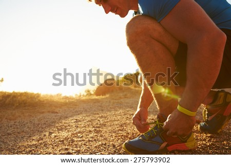 Close up of a man doing up his running shoes - stock photo