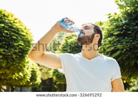 close up of a man drinking water from a bottle outside - stock photo