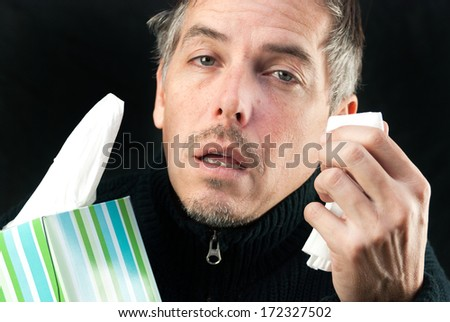 Close-up of a man exhausted by allergies/cold/flu holding a tissue and the box. - stock photo