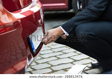 Close-up Of A Man Fixing New Empty White Number Plate On His Red Care - stock photo