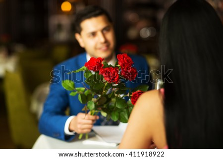close-up of a man giving flowers to a woman on a date in a restaurant