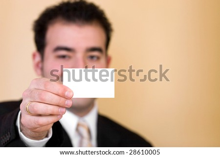 Close up of a man holding a business card up.  Plenty of copyspace for your logo or design.  Shallow depth of field with focus on the hand and card.