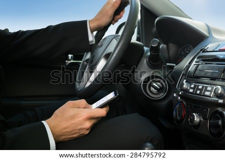 Close-up Of A Man Holding Cellphone While Driving Car - stock photo