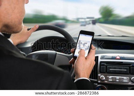 Close-up Of A Man Holding Cellphone With Message Notification While Driving Car - stock photo