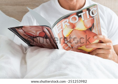 Close-up Of A Man Holding Magazine At Home - stock photo