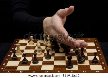 close-up of a man in a black sweater stretched out her hand to the opponent on wooden chessboard on a black background